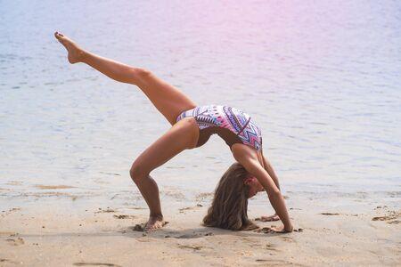 schoolgirl making gymnastics on seashore Standard-Bild