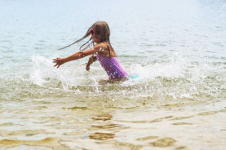 Happy little girl playing in shallow water waves