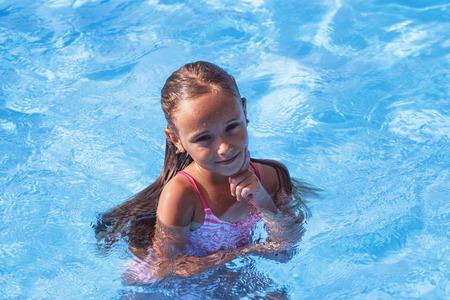 Bella bambina nuota in piscina, bambina carina in piscina in day.little soleggiato ragazza.