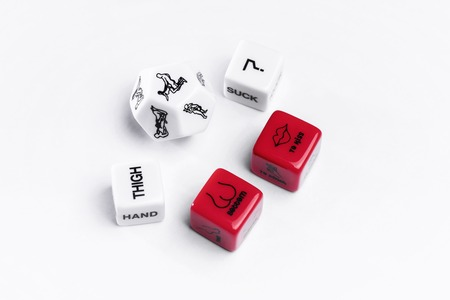 Game stones for sex games. Adult toys for sex games. White and red stones.Cubes with Kama Sutra poses for sex games. Playing cubes of red and white color for sexual games.