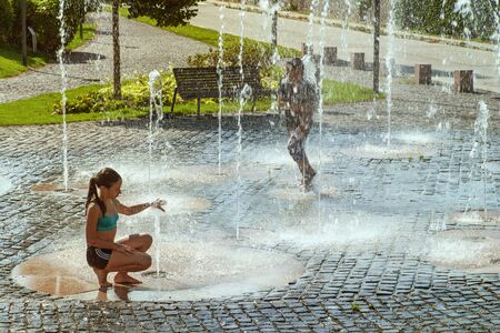 Children on a sunny summer day are poured water from a fountain.Children happily in shallow clean water on of city fountain on warm bright summer day.