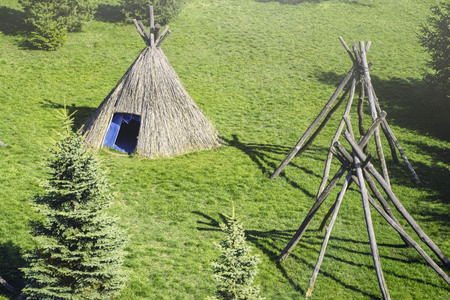 Straw wigwam on a glade on a sunny spring day. Wigwam type thatch huts .