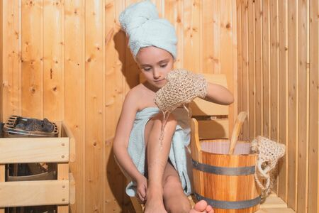 Young Girl relaxing in sauna,girl in a spa treatment in a traditional sauna with a brush for skin and a washcloth.