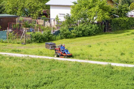 Worker mowing grass in city park. Sunny summer day.Mature man driving grass cutter in a sunny day.Gardener driving a riding lawn mower in a garden