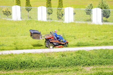 Worker mowing grass in city park. Sunny summer day.Mature man driving grass cutter in a sunny day.Gardener driving a riding lawn mower in a garden 免版税图像