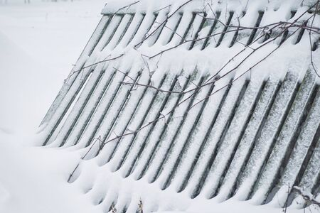 Winter landscape. Season winter. The wooden fence is noticeable with snow.