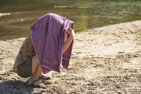 The girl hid her face from the bright sun under a towel.The girl is sitting on the beach with a towel on her head.