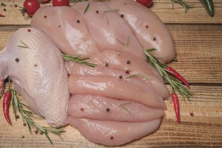 .Raw chicken meat on wooden board. Healthy eating.Raw, fresh chicken meat platter on a wooden surface with spices for cooking. 写真素材