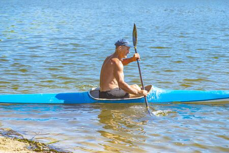 A man swims in a canoe on the river. A man in a boat on a sunny summer day. Blue and yellow boat.Man paddling a blue and yellow kayak on the river near the shore. Kayaking concept 写真素材 - 131977140