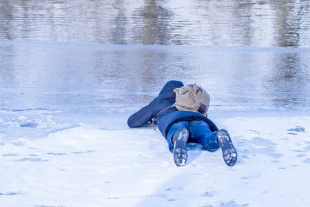 The man lies on ice in the winter,a man lies on the ice of the winter river and looks through the ice .