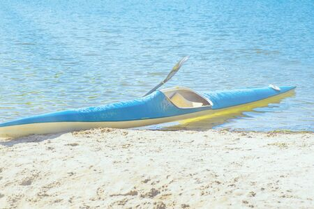 Kayak on the beach. Kayak blue and yellow. Boat on the river bank. Summer sunny day. Kayak sport.Kayaking concept. 写真素材 - 131977242