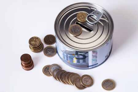TFinancial risk and safety concept.he concept of money. A piggy bank in the form of a tin can and, next to the piggy bank, money bills and coins are laid out.