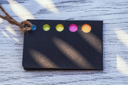 .Business idea concept.Black card with colored bookmarks for notes. Card for notes. Background.