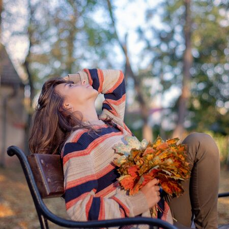 Beautiful girl sits on a bench in autumn. In the girls hand holds autumn leaves. girl sitting at bench in autumn park.