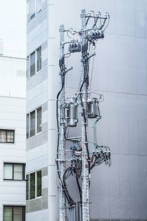 Modern poles with electricity cables on the background of a residential building, poles with electric wires, telecommunication pole .background.