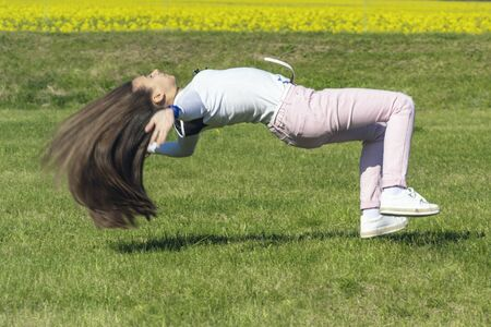 Girl on the nature does acrobatic stunts.A young girl jumping on the grass, a girl in the nature of sports. 写真素材