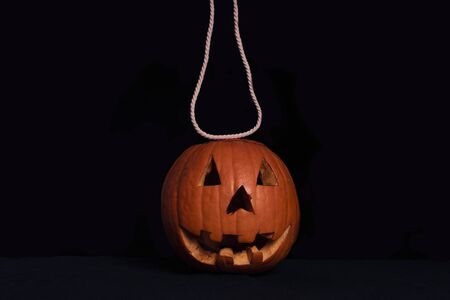 Pumpkin suspended on a rope. Preparation for Halloween.Orange squash on a black background with a white rope. 写真素材