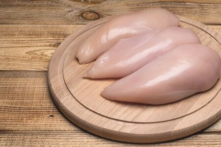 Fresh raw chicken fillet on a wooden cutting board.Raw chicken breasts and spices on wooden cutting board, close up view.