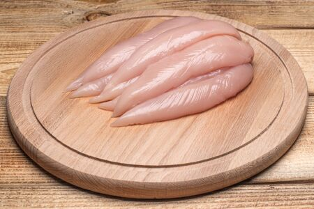 Small inner chicken fillet on a wooden cutting board.Raw, fresh small inner chicken fillet.