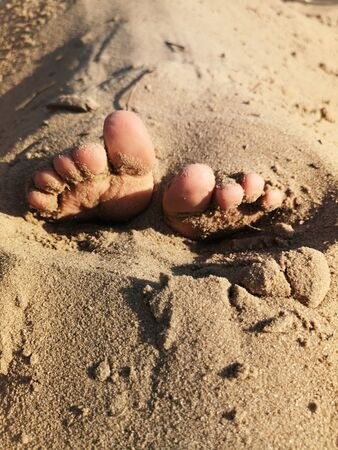 Stuck baby feet in sand on sea beach on sunny day.Baby fingers in the sand