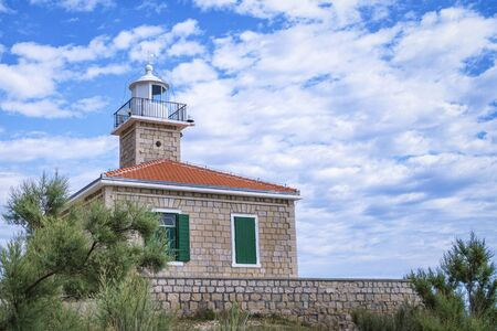 Lighthouse on a hill against the blue sky. Croatia lighthouse Makarska.Lighthouse on the island against the cloudy sky, Croatia. 写真素材