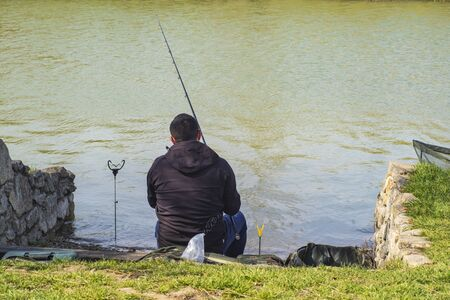 Spring warm day man with fishing rod , man standing on the riverbank fishing fish.A man on the riverbank with a fishing rod catches a fish. Stock Photo