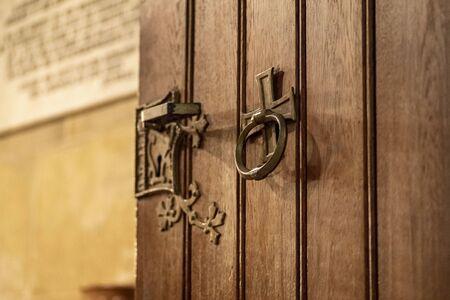 Door handle on the door.Nice brown wooden door with fittings. It is the entrance door to the church. 写真素材