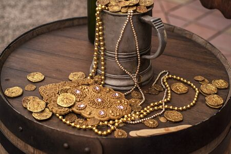 Jack Sparrow coins.Artificial gold coins and a decoration on a wooden barrel. A filled mug with gold artificial coins.