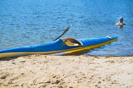 Kayak on the beach. Kayak blue and yellow. Boat on the river bank. Summer sunny day. Kayak sport.Kayaking concept.