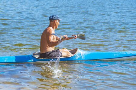 A man swims in a canoe on the river. A man in a boat on a sunny summer day. Blue and yellow boat.Man paddling a blue and yellow kayak on the river near the shore. Kayaking concept