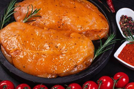 Raw meat in the marinade.Marinated Chicken Breast with spices and rosemary on a black plate.