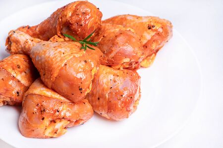 Raw marinated chicken legs for grill and bbq.Chicken legs in a red marinade on a white plate. Top view. Chicken meat close-up.. Dietary meat. Cooking.Isolate. Reklamní fotografie