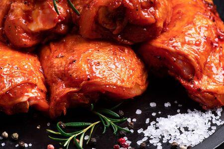 Rauwe kip gewatteerd in rood, tomatenmarinade op een zwarte plaat en kruiden. Rauw vlees in de marinade. Dieetvlees.