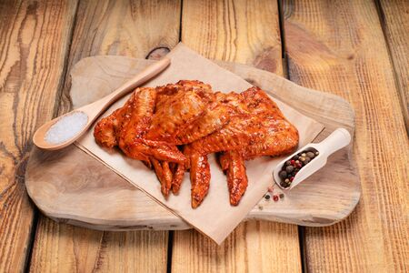 Chicken marinated meat.Raw pickled chicken wings on a blue plate on a wooden background.