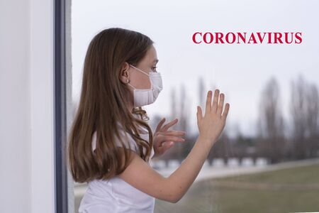 A little girl sits at the window in a protective mask, wants to go outside, but it s impossible, there is a coronavirus, the girl is sad. Girl in a protective mask by the window. Banco de Imagens