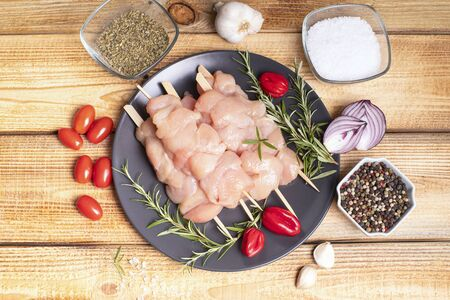 Kebab on a wooden background. Top view.Raw chicken skewers with tomatoes and vegetables.