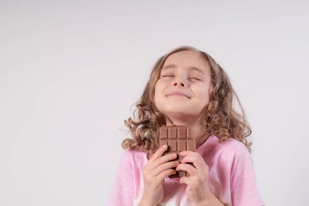 Girl and chocolate.Little girl on a light background with chocolate in her hands.