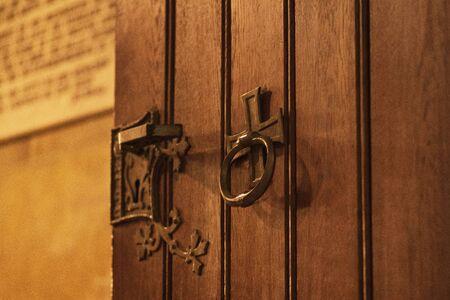 Door handle on the door.Nice brown wooden door with fittings. It is the entrance door to the church.