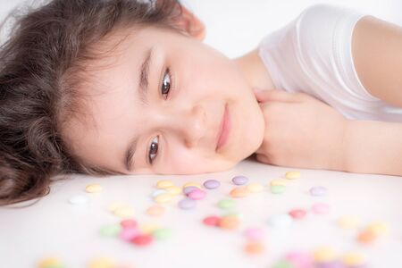 Children and chocolate. A cheerful girl plays and eats chocolate multi-colored round candies on a light background.Joyful girl with sweets.
