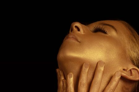 Golden Womans Face Closeup. Futuristic Gilded Make-up. Painted Skin.A beautiful girl in a golden mask on her face . Beauty concept.