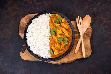 White rice with chicken and vegetables and curry sauce. Indian dish with vegetables and chicken on a black plate on a wooden kitchen board with a wooden spoon and fork..tasty fillet chicken curry with rice on a plate on the table.