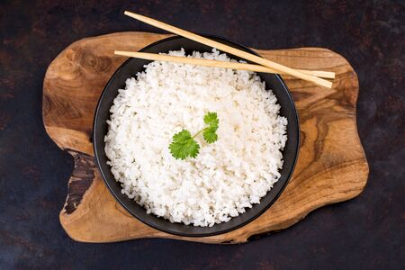 White rice on a black plate with chopsticks on a wooden table.top view. Zdjęcie Seryjne