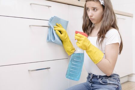 Tired frustrated and exhausted cleaning woman .A young girl is tired of cleaning the house. The girl is not willing to wash the kitchen. Cleaning the kitchen in protective gloves.