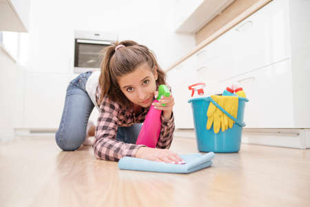 Girl cleaning the house. House cleaning service.young housewife polishing floor with furniture polish. Imagens