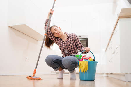 A tired young cleaning lady is resting in the kitchen after cleaning the house sitting on the floor with a cleaning supplies bucket and a mop.Professional cleaning service concept. Imagens