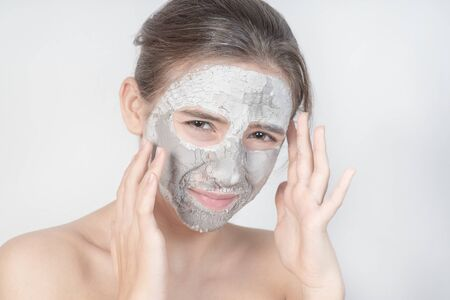 Natural Makeup Applying Grey Clay Mask On Face.Young girl in a cosmetic gray mask. Gray cosmetic clay on the girl's face tightens the skin.