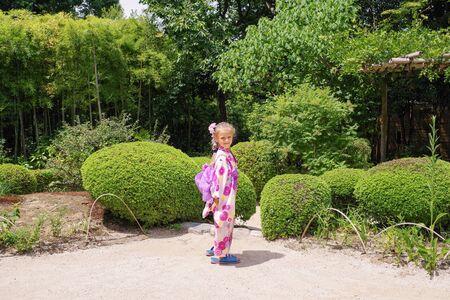 Japanese kimono on european girl.Little european girl in japanese kimono in japanese little garden.