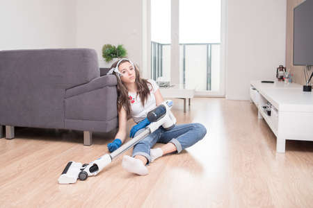 woman using vacuum cleaner in the living room.Young girl cleans the apartment. Tired girl after cleaning sits on the floor with a vacuum cleaner.