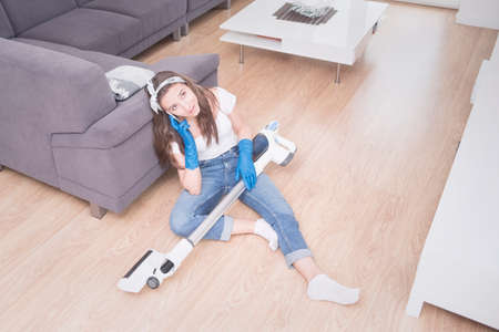 Young girl cleans the apartment. Tired girl after cleaning sits on the floor with a vacuum cleaner and speaks on the phone.