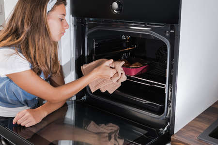 Chicken meat for roasting. The girl puts meat in the baking package in the oven for baking.